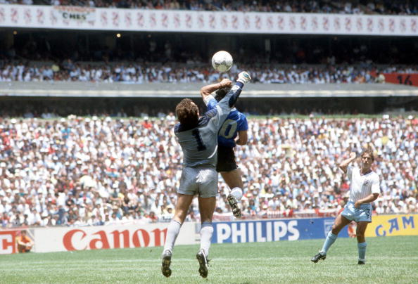 1986 World Cup Quarter Final, Azteca Stadium, Mexico, 22nd June, 1986, Argentina 2 v England 1, Argentina's Diego Maradona scores his side's first goal past English goalkeeper Peter Shilton by use of his hand, Maradona later claimed that the goal was scor