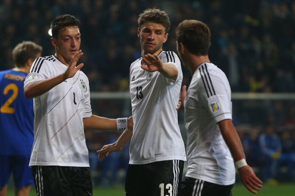 ASTANA, KAZAKHSTAN - MARCH 22:  Thomas Mueller (C) of Germany celebrates scoring the 4th team goal with his team mates Mesut Oezil (L) and Mario Goetze (R) during the FIFA 2014 World Cup qualifier group C match between Kazakhstan and Germany