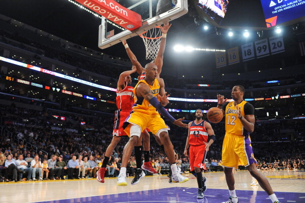 LOS ANGELES, CA - MARCH 22: Kobe Bryant #24 of the Los Angeles Lakers passes the ball in the lane to teammate Dwight Howard #12 during their game against the Washington Wizards at Staples Center on March 22, 2013 in Los Angeles, California.
