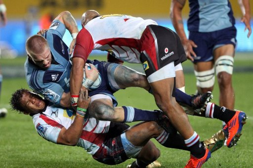 Blues' Gareth Anscombe is tackled by Lions' Elton Jantjies (L) and Lionel Mapoe (R), in Auckland, on May 11, 2012