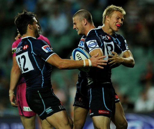 Waratahs' Robert Horne (C) is congratulated by teammates after scoring a try against Bulls, in Sydney, on May 11, 2012