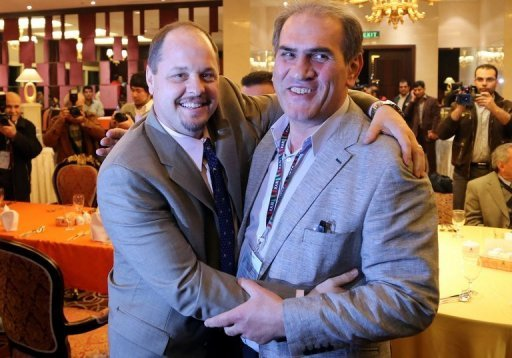 USA Wrestling's Rich Bender (L) poses with Iran's wrestling federation head Hojatollah Khatib on February 20, 2013