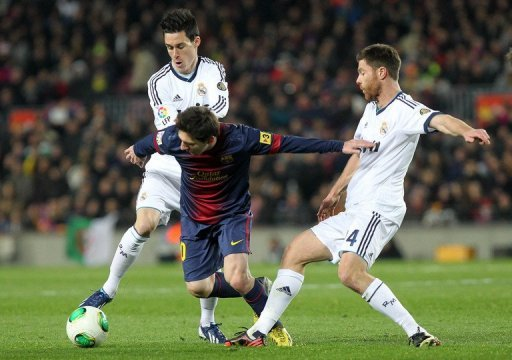 Barcelona's Lionel Messi tries to find a way through Real Madrid's Jose Callejon (L) and  Xabi Alonso February 26, 2013