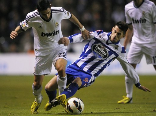 Real Madrid's Angel di Maria (L) is tackled by Deportivo's Pizzi during their Spanish league match on February 23, 2013