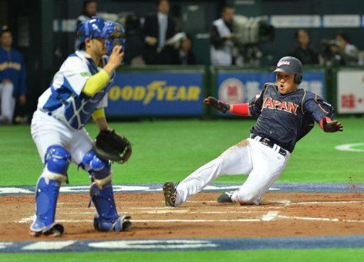 Japan's Seiichi Uchikawa (R) arrives at the home plate in Fukuoka on March 2, 2013