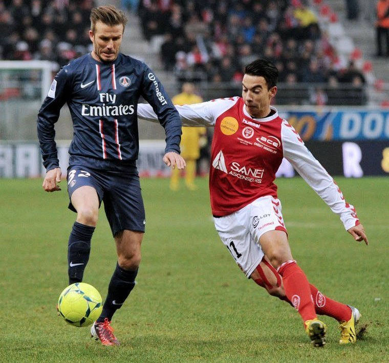 Paris Saint-Germain's David Beckham (L) clashes with Reims' Diego Rigonato on March 2, 2013 in Reims