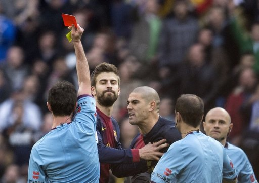 Barcelona goalkeeper Victor Valdes (C) gets a red card from referee Perez Lasa in Madrid on March 2, 2013