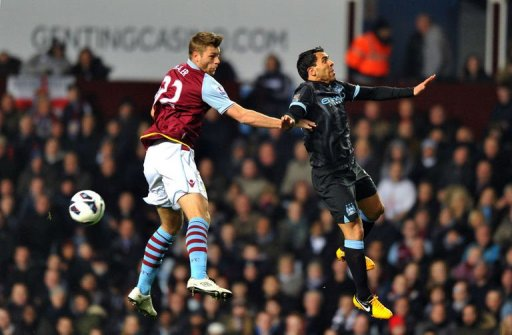 Manchester City's Carlos Tevez (R) jumps with Aston Villa's Nathan Baker in Birmingham on March 4, 2013