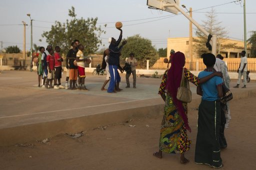 Youngsters play basketball at the former