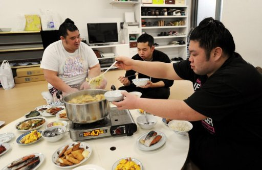 Sumo wrestlers Genkaiho (R) and Migikataagari (L) eat with hair dresser Tokonao at a sumo stable on February 14, 2013