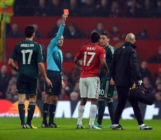 Turkish referee Cuneyt Cakir (2nd L) shows Manchester United's Nani the red card in Manchester on March 5, 2013