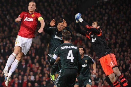 United's Nemanja Vidic (L) jumps for the ball with Real's Raphael Varane (C) at Old Trafford on March 5, 2013