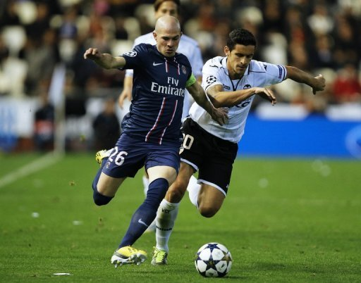 PSG's Christophe Jallet (L) fights for the ball with Valencia's Ricardo Costa during the first leg on February 12, 2013