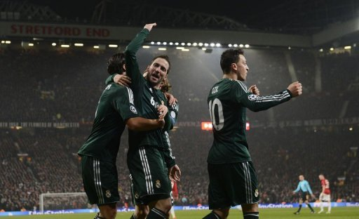 Real Madrid's Gonzalo Higuain (C) celebrates setting up his team's second goal at Old Trafford on March 5, 2013