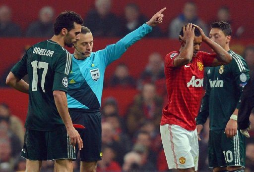 United midfielder Nani (R) holds his head as referee Cuneyt Cakir sends him off at Old Trafford on March 5, 2013