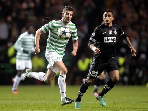 Celtic's Charlie Mulgrew (L) vies with Arturo Vidal of Juventus during the first leg at Celtic Park on February 12, 2013