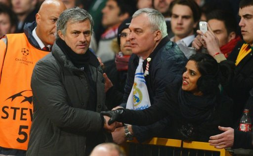 Real Madrid's manager Jose Mourinho (L) is greeted by fans as he leaves the pitch at Old Trafford on March 5, 2013