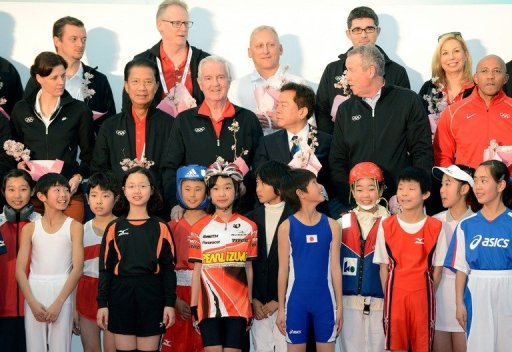 International Olympic Committee (IOC) members pose with children in Tokyo on March 6, 2013