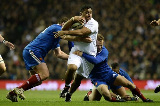 Mako Vunipola (centre) is tackled during a rugby match between England and France in London on February 23, 2013