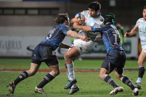 Racing Metro's Fabrice Estebanez (C) is tackled by Montpellier's Thomas Combezou (L) and Paul Bosch, March 8, 2013