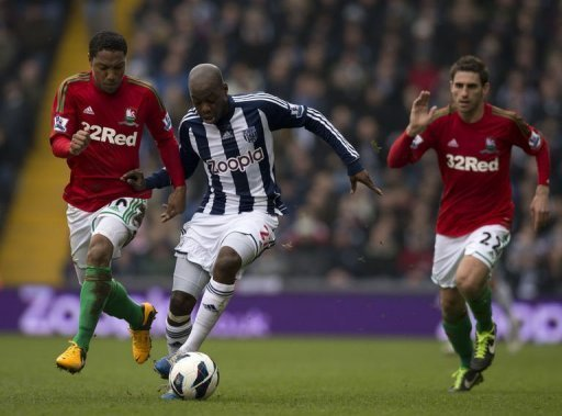West Brom's Youssouf Mulumbu (C) runs against Swansea's Jonathan de Guzman (L) and Angel Rangel, March 9, 2013