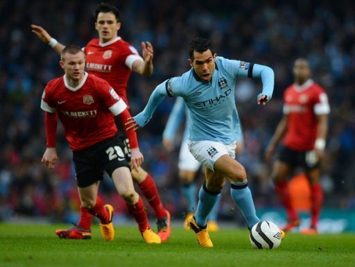 Manchester City forward Carlos Tevez gets away from Barnsley's Ryan Tunnicliffe on March 9, 2013