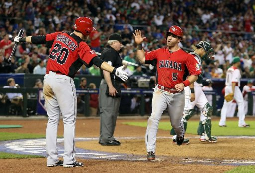 Taylor Green (R) of Canada high fives Michael Saunders after scoring on March 9, 2013 in Phoenix, Arizona