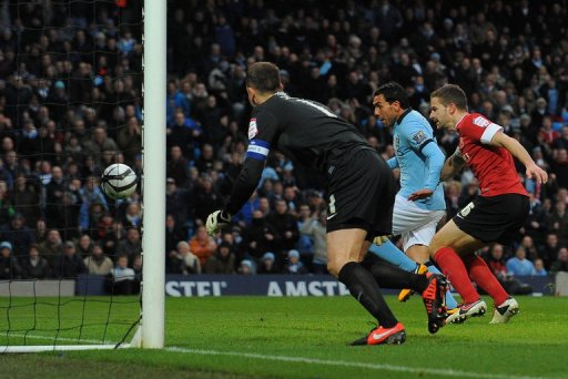 Manchester City forward Carlos Tevez scores the opening goal against Barnsley on March 9, 2013