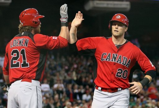 Michael Saunders (R) of Canada high-fives Adam Loewen after scoring a first-inning run against Mexico on March 9, 2013