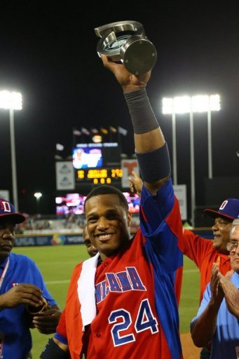 Robinson Cano of the Dominican Republic holds the MVP trophy after defeating Puerto Rico at the WBC on March 10, 2013