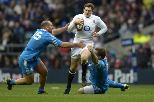 England full-back Alex Goode (C) is tackled by Italy's Davide Giazzon (L) at Twickenham on March 10, 2013