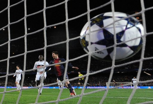 Barcelona's Lionel Messi celebrates scoring against AC Milan at Camp Nou in Barcelona on March 12, 2013