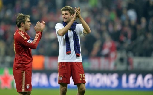 Bayern Munich's Philipp Lahm (L) and Thomas Mueller applaud after the match in Munich on March 13, 2013