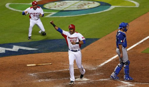 Alex Rios celebrates scoring the game-winning run against Italy on March 13, 2013
