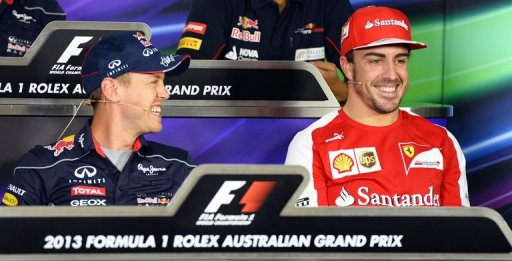 Sebastian Vettel (L) shares a lighter moment with rival Fernando Alonso at a press conference on March 14, 2013