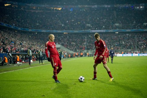 Bayern's Arjen Robben (L) and Thomas Mueller (R) play at the Allianz arena in Munich on March 13, 2013