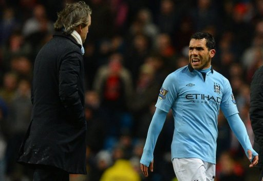 Manchester City's Carlos Tevez speaks to manager Roberto Mancini during the match against Barnsley March 9, 2013