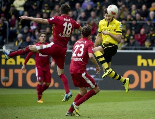 Dortmund's striker Robert Lewandowski (R) heads to score in Dortmund on March 16, 2013