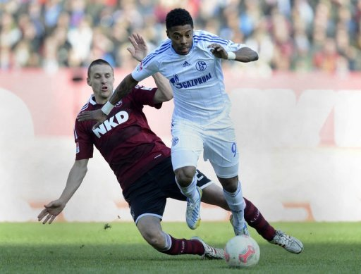 Schalke's Michel Bastos (R) and Nuremberg's Timmy Simons fight for the ball, March 16, 2013 in Nuremberg