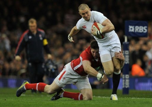 England's wing Mike Brown (R) is tackled in Cardiff, on March 16, 2013