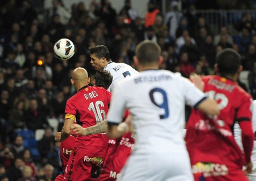 Real Madrid's forward Cristiano Ronaldo (C) heads the ball to score in Madrid on March 16, 2013