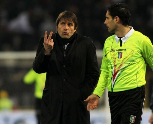 Juventus head coach Antonio Conte (L) talks with a referee assistant on March 16, 2013 in Bologna