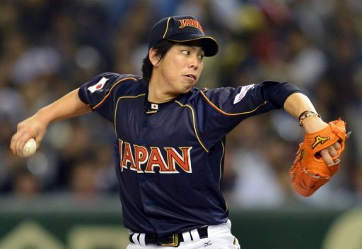 Japan's Kenta Maeda pitches during their WBC game against the Netherlands on March 10, 2013