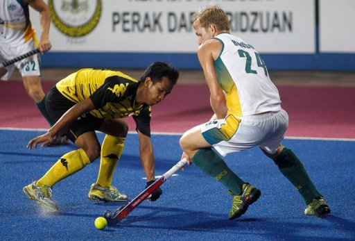 Faizal Saari (left) fights for the ball with Christopher Bausor in Ipoh on March 17, 2013.