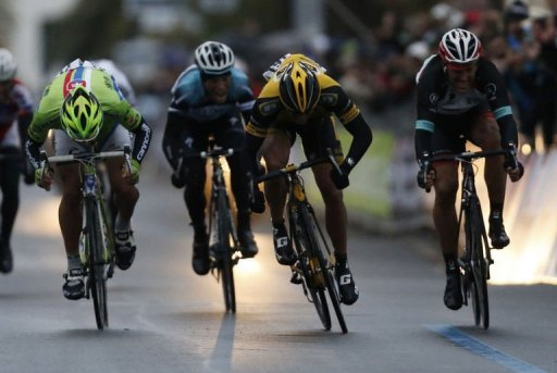 Gerald Ciolek (yellow) crosses the finish line to win the 104th Milan San Remo spring classic on March 17, 2013