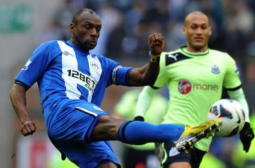 Wigan's Emmerson Boyce (L) clears the ball away from Newcastle's Yoan Gouffran in Wigan on March 17, 2013