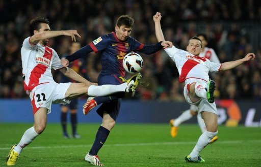 Lionel Messi (C) is blocked by Rayo Vallecano's Jordi Figueras Montel (L) and Tito during their match on March 17, 2013