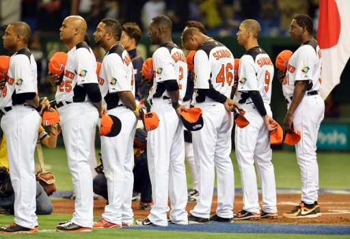 Netherlands manager Hensley Meulens (R) and players listen to the national anthem ahead of a WBC game on March 10, 2013