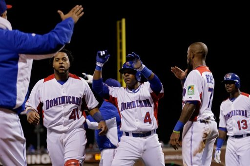 Miguel Tejada (C) celebrates with Carlos Santana (L) and Jose Reyes after scoring in the fifth inning on March 18, 2013