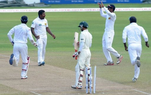 Rangana Herath (2nd left) celebrates with teammates after dismissing Nasir Hossain (centre) in Colombo on March 19, 2013